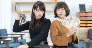 お金を持っている女性と、貯金箱をひっくり返している女性の画像